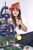 Girl with Christmas-tree decorations. The girl in the hat of Santa Claus and Christmas tree toys in their hands Royalty Free Stock Images
