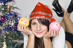 Girl with Christmas-tree decorations. The girl in the hat of Santa Claus and Christmas tree toys in their hands Stock Photography