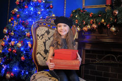 The girl at the Christmas tree with a gift in hands Royalty Free Stock Photo