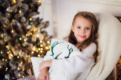 Girl at Christmas, xmas tree in the background, beautiful young kid wrapped in a blanket, she smiles Royalty Free Stock Photos