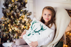 Girl at Christmas, xmas tree in the background, beautiful young kid wrapped in a blanket, she smiles Royalty Free Stock Image