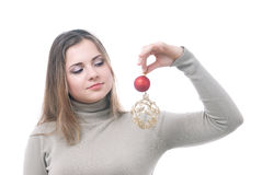 Girl with the christmass toys in her hand. Portrait of girl looking at two christmass toys in her hand - red and gold isolated on white Stock Photo