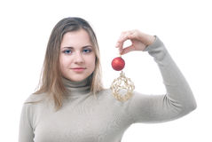 Girl with the christmass toys in her hand. Portrait of girl looking at two christmass toys in her hand - red and gold isolated on white Stock Images
