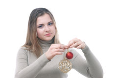 Girl with the christmass toys in her hand. Portrait of girl looking at two christmass toys in her hand - red and gold isolated on white Royalty Free Stock Image