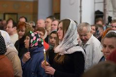 The girl in the church. Belarus, Gomel, on April 8, 2018. The Nikolsky Monastery. The celebration of Orthodox Easter. A crowd of believers in the church. Many stock photography