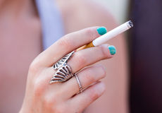 Girl with cigarette. Young girl holds cigarette in her hand Stock Photo