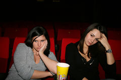Girl is in cinema. Girls are in the cinema, look the boring film Royalty Free Stock Images