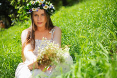 Girl with circlet of flowers. Portrait of a girl with circlet of flowers. She is sitting in a green meadow Stock Photography