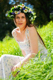 Girl with circlet of flowers. Portrait of a girl with circlet of flowers. She is sitting in a green meadow Stock Image