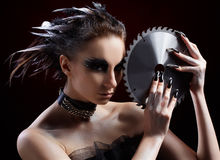 Girl with circular saw. Portrait of beautiful girl with bird of prey fantasy make-up with circular saw blade Royalty Free Stock Images