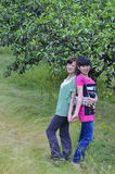 Girl and citrus orchard. Two beautiful chinese girls were standing in citrus orchard with cheerful smiling royalty free stock photos