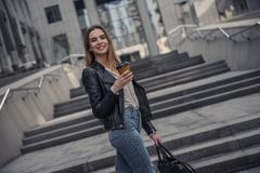 Girl in city. Beautiful young girl in casual clothes is holding cup of coffee, looking at camera and smiling while walking in the city center royalty free stock photo