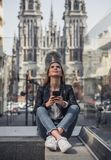 Girl in city. Beautiful young girl in casual clothes is holding a smartphone, looking upward and smiling while resting in city center stock photography