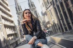Girl in city. Beautiful young girl in casual clothes is looking away and dreaming while resting in city center royalty free stock images