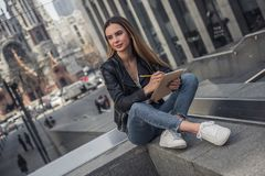 Girl in city. Beautiful young girl in casual clothes is making notes, looking away and smiling while resting in city center stock photography