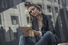 Girl in city. Beautiful young girl in casual clothes is making notes and smiling while resting in city center, view from behind the glass stock image