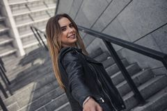 Girl in city. Beautiful young girl in casual clothes is stretching her hand, looking at camera and smiling while walking in the city royalty free stock images