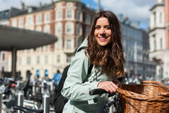 Girl in the city with bike with a parking space for bicycles backgroung Royalty Free Stock Image