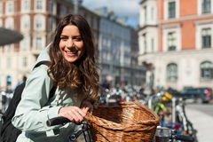 Girl in the city with bike with a parking space for bicycles backgroung Stock Photo