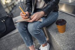 Girl in city. Cropped image of beautiful young girl in casual clothes making notes while resting in city center, cup of coffee is near stock image