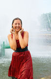 Girl in a city fountain. The young laughing girl in wet clothes in a city fountain Royalty Free Stock Images