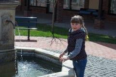Girl in city fountain Stock Image
