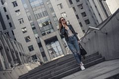 Girl in city. Full-length portrait of beautiful young girl in casual clothes and sun glasses talking on the mobile phone and smiling while walking in the city stock photo
