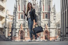 Girl in city. Full-length portrait of beautiful young girl in casual clothes holding a smartphone and a bag and smiling while walking in the city center stock images