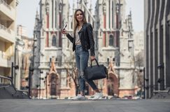 Girl in city. Full-length portrait of beautiful young girl in casual clothes holding sun glasses and a bag and smiling while walking in the city center stock photography