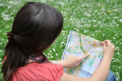 Girl with the city map. Girl explores the city map in city park Stock Photography