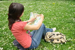 Girl with the city map in park. Girl explores the city map in city park Royalty Free Stock Images