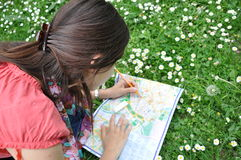 Girl with the city map in park. Girl explores the city map in city park Stock Photos