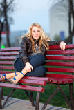 Girl in a city park on a bench. Beautiful girl sitting on a bench in a city park in the evening Stock Photography