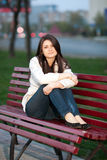 Girl in a city park on a bench. Beautiful girl sitting on a bench in a city park in the evening Royalty Free Stock Images