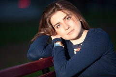 Girl in a city park on a bench. Beautiful girl sitting on a bench in a city park in the evening Royalty Free Stock Image