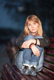 Girl in a city park on a bench. Beautiful girl sitting on a bench in a city park in the evening Royalty Free Stock Photography