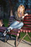 Girl in a city park on a bench. Beautiful girl sitting on a bench in a city park in the evening Stock Image