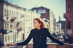 Girl city portrait. Portrait of red-haired girl on the background of the city royalty free stock photos