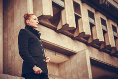 Girl city portrait. Portrait of red-haired girl on the background of the city building stock photo