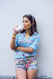 The girl in the city in shirt drinking a milkshake, fresh juice, enjoying, brunette, tanned, sensual make-up, recreation Royalty Free Stock Photography