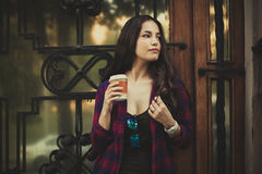 Girl in the city with smartphone and takeaway coffee stock photography