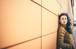 Girl on the city street near wall Stock Photos