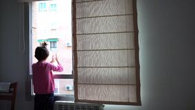 Girl clapping in the window in support of people who fight against the coronavirus