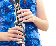 Girl with clarinet. Beautiful girl in a blue dress isolated on white background holding clarinet in his hands Royalty Free Stock Image