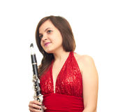 Girl with clarinet. Beautiful girl in red dress isolated on white background holding clarinet Royalty Free Stock Photography