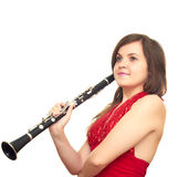 Girl with clarinet. Beautiful girl in red dress isolated on white background holding clarinet Royalty Free Stock Photo