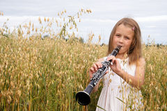 Girl with clarinet. Young girl with clarinet at cornfield stock images