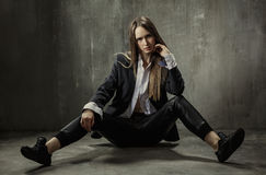The girl in classic jacket, blouse and leather pants sits on a b Stock Images
