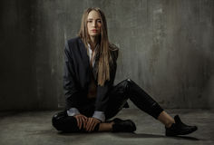 The girl in classic jacket, blouse and leather pants sits on a b Stock Image