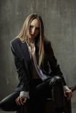 The girl in classic jacket, blouse and leather pants sits on a b. Ackground of gray concrete wall Royalty Free Stock Photos